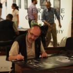 [:en]Pierre Poulain signing the prints.[:he]פייר פאולין חותם על ההדפסים
